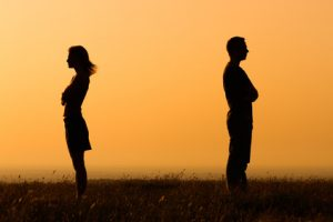 couple facing away from each other in front of a bright orange sky